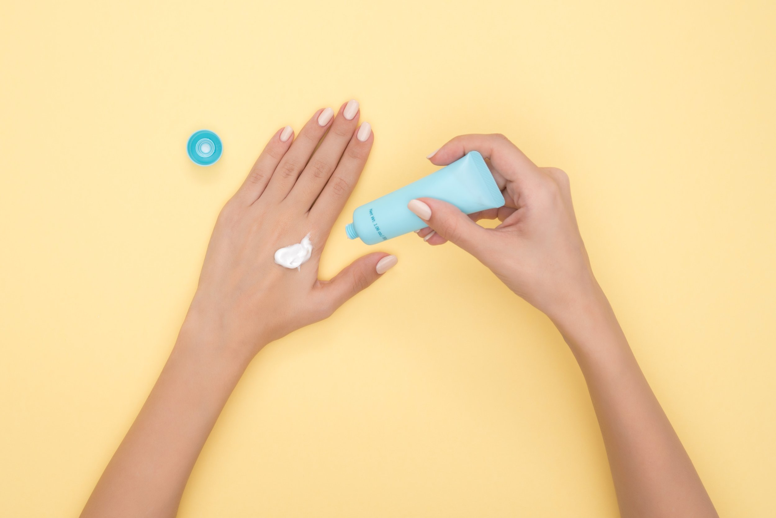 A woman puts lotion on her hand