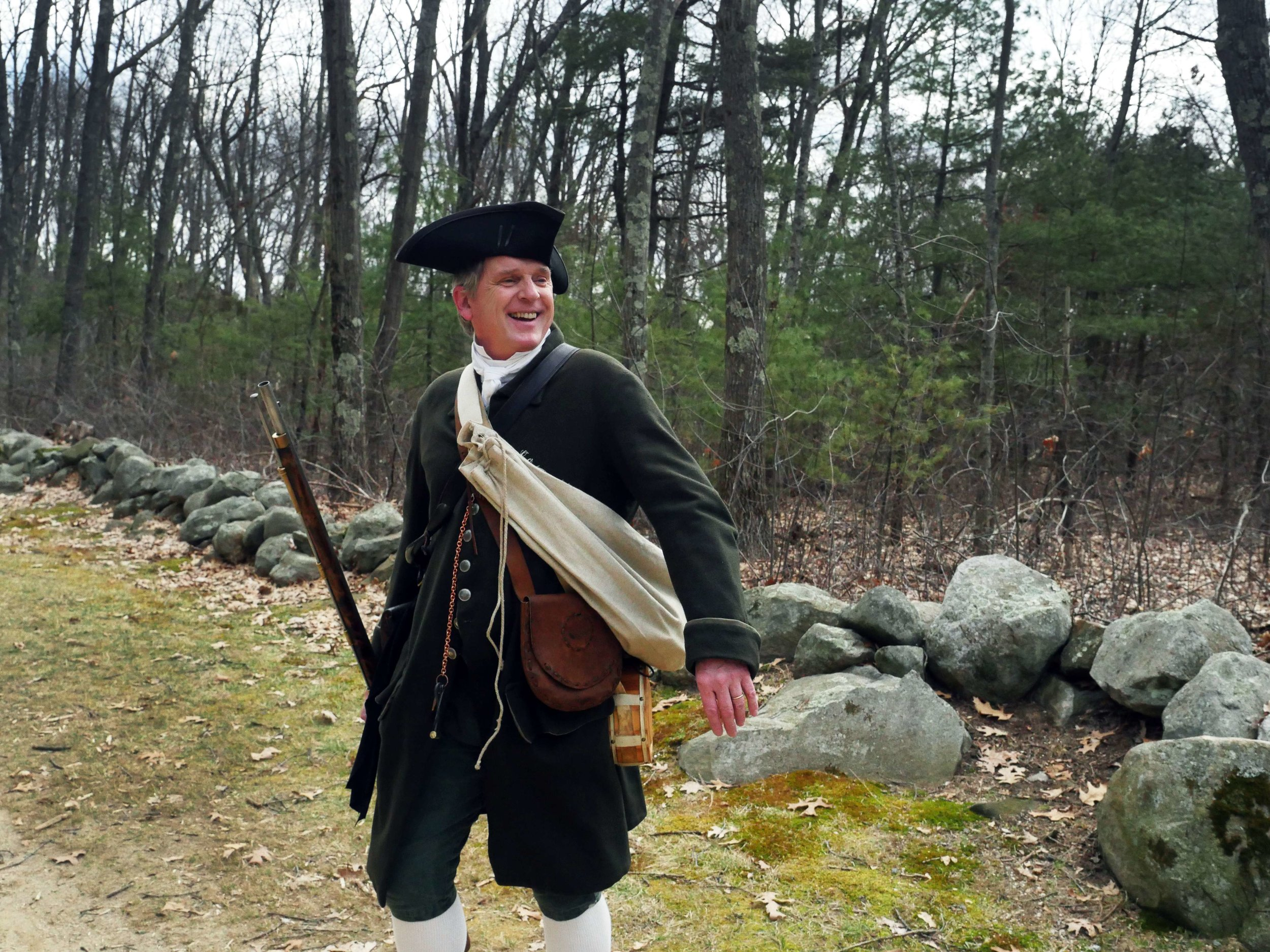 "Lincoln, MA - April 14th, 2018 - Lincoln Minuteman Company Sergeant Major, Hannes Klein, laughs as he heckles a passer byer for wearing the color red on the day of the Battle of Lexington and Concord reenactments. Klein, who used to participate in theatre says, ""the part I like the most is mingling with the crowd."""
