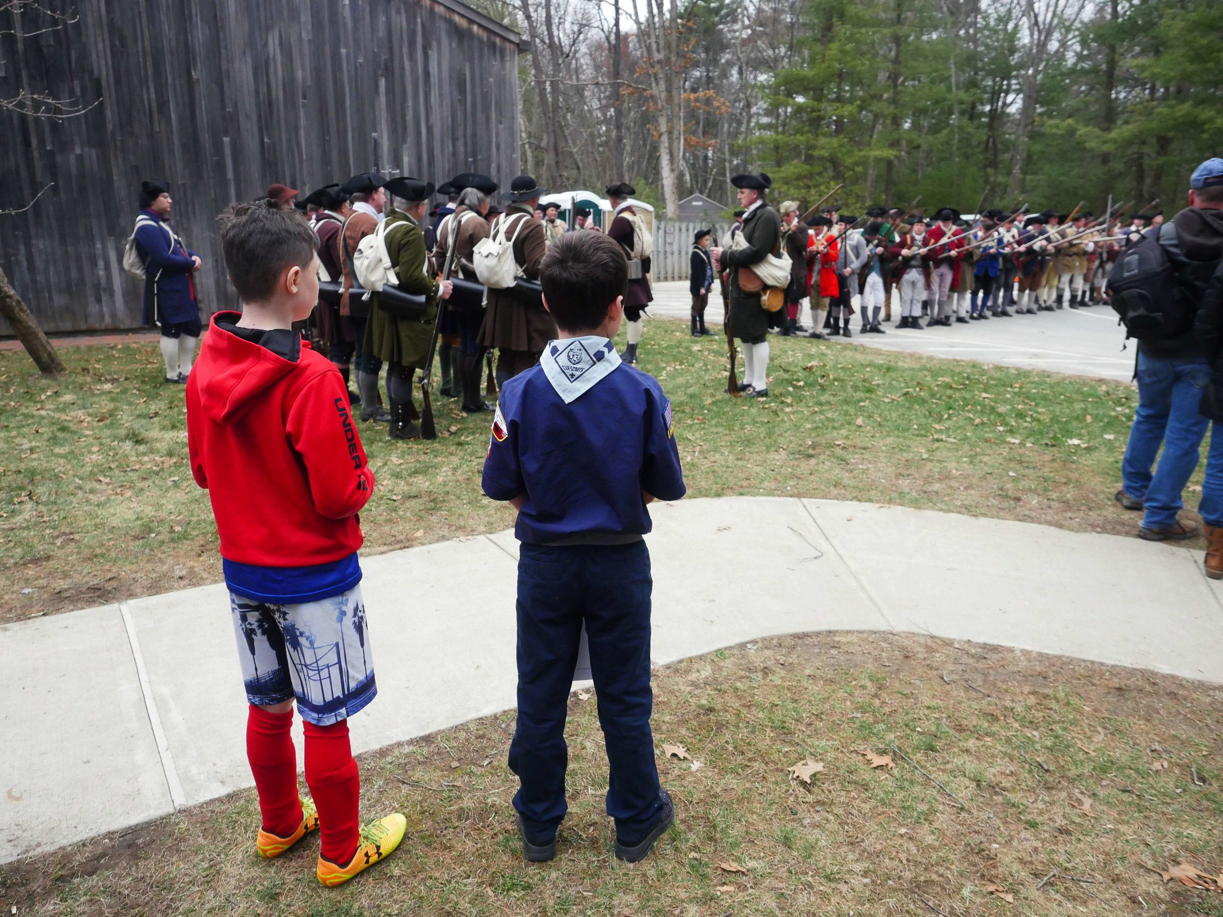 Lincoln, MA - April 14th, 2018 - Two young boy scouts look on as Hannes Klein rallies the troops for the 243rd anniversary of the Battles of Lexington and Concord. Klein says that the battle still garners a large crowd even in the inclement of weather.
