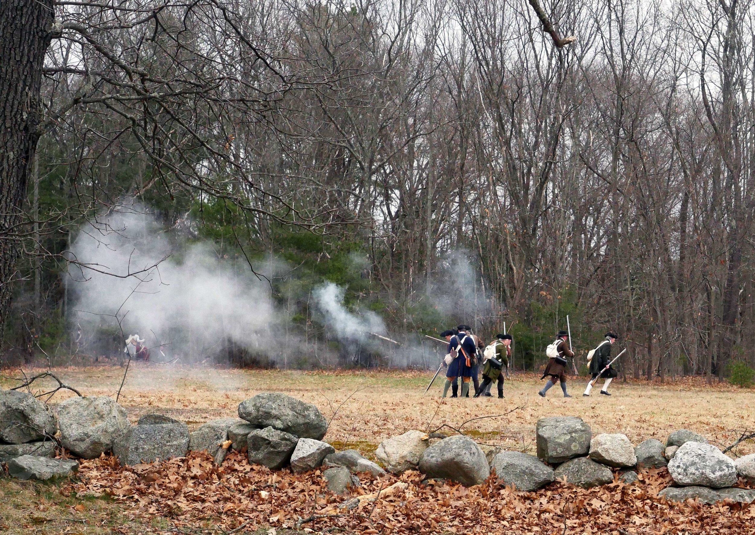 Lincoln, MA - April 14th, 2018 - Hannes Klein leads his men from the fourth battalion of the Lincoln Minuteman Company away from enemy fire during the Battles of Lexington and Concord. The reenactors do not use bullets in their guns, instead relying on powder to convey the shots.