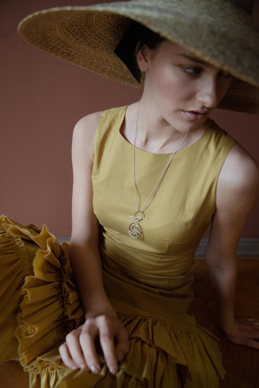 Ohuesta puuvillasta valmistettu Tutudress 590 e,  Anna Ruohonen Paris . Olkihattu 225 e,  éN Hats . Hopeinen kaulakoru ja riipus ovat Mile-Stylen omaa tulevaa mallistoa, suunnittelija  Mia Maljojoki .