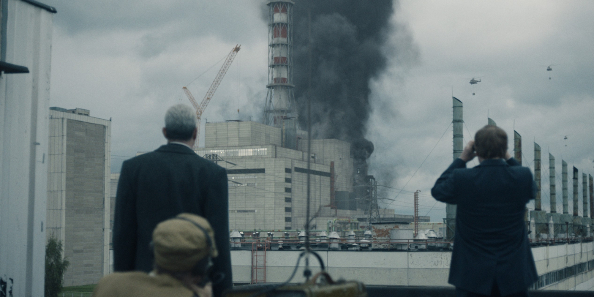 Legasov and Shcherbina watch helicopters dropping sand and boron over the flaming reactor.