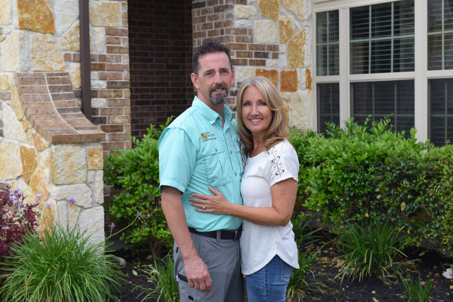 Mark and Wendy in front of home.jpg