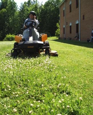 Nun mowing grass