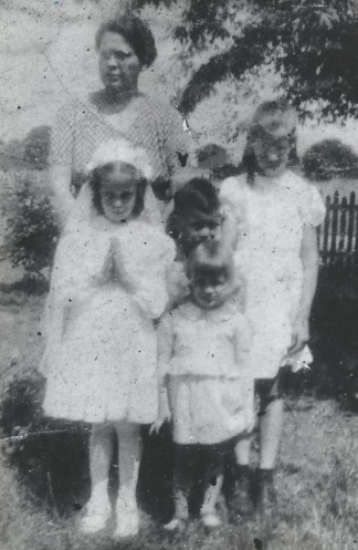 Cissy on her First Communion Day May 16, 1948 .  Her beautiful and self-giving  mother Betty stands at back gathered around her children:  Cissy, Bill, Betsy and Barb