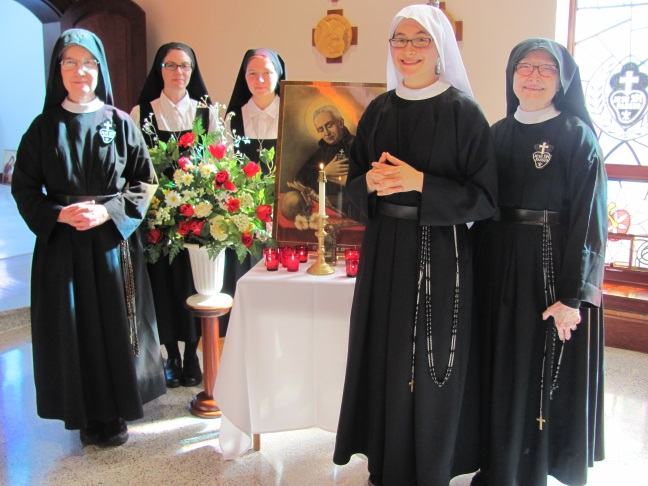 Sr. Lucia Marie with Mother Catherine Marie and fellow novitiate members gather around the image of our Holy Founder and his relic