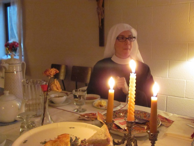 Sr. Maria Faustina caught in the middle of enjoying some orange slices. The finger sandwiches can be seen in the foreground
