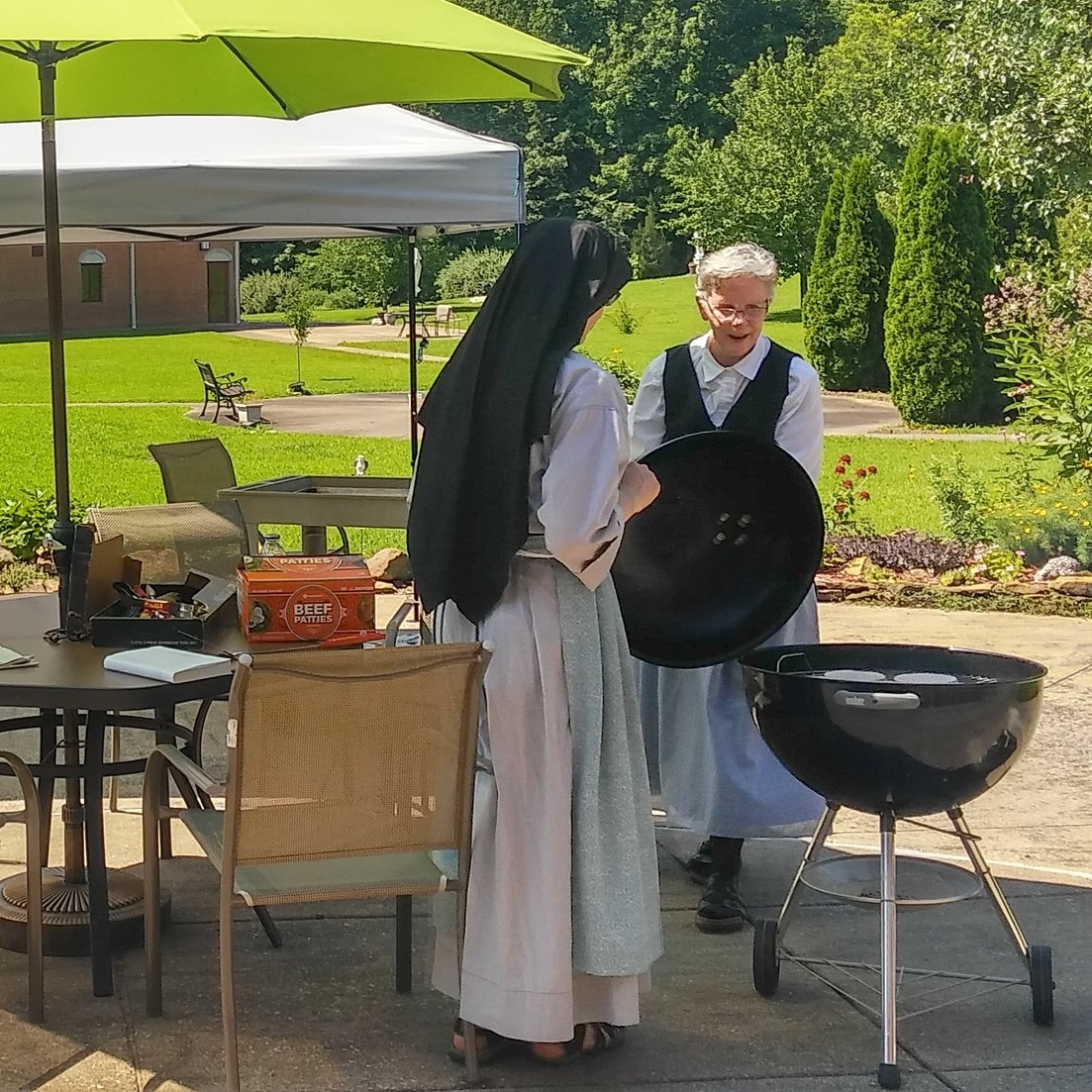 Christie giving Sr. Lucia Marie expert pointers on grilling hamburgers.