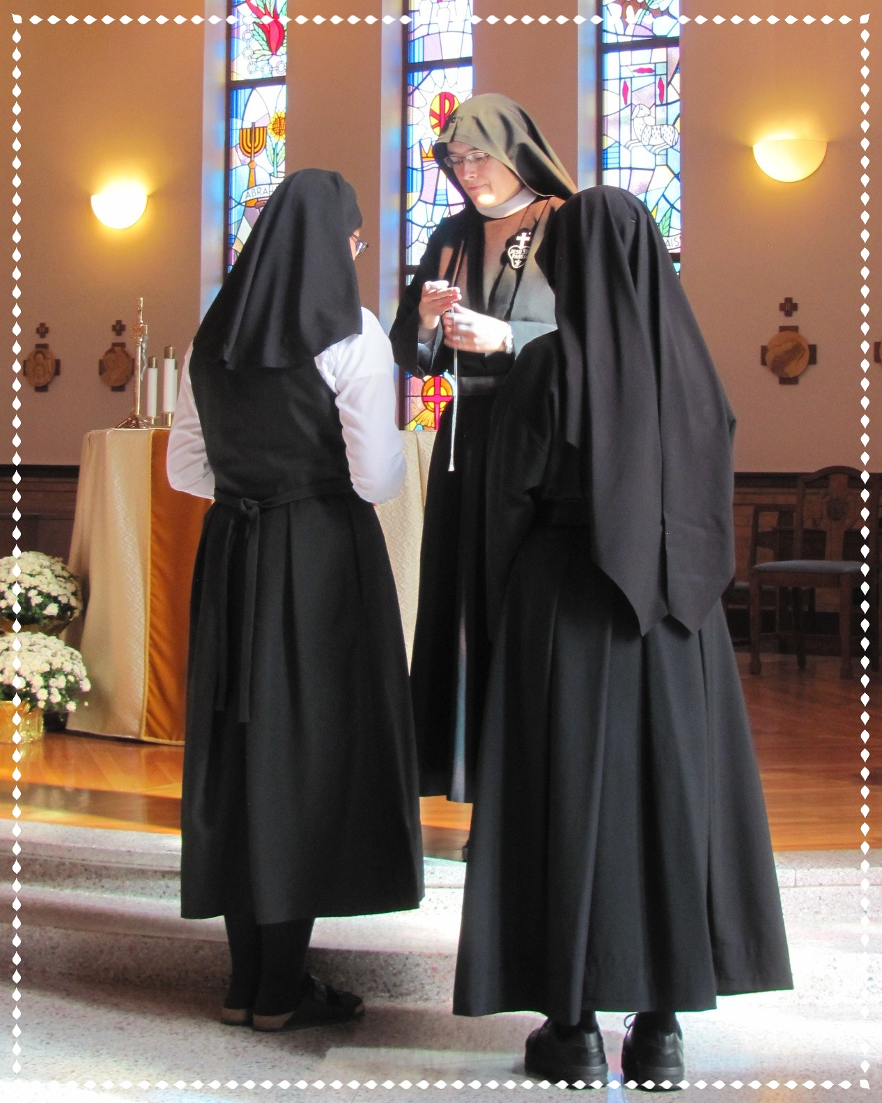 Theresa receives the postulant crucifix from Mother John Mary while Sr. Mary Veronica, the novice mistress, looks on.