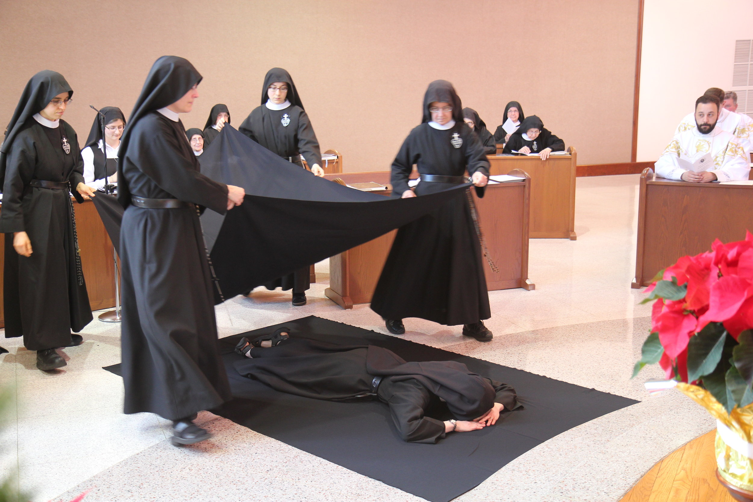While she lies before the altar, the nuns and guests join in singing the Litany of the Saints, invoking their aid for Sister Cecilia Maria as she prepares for her perpetual consecration to Christ.