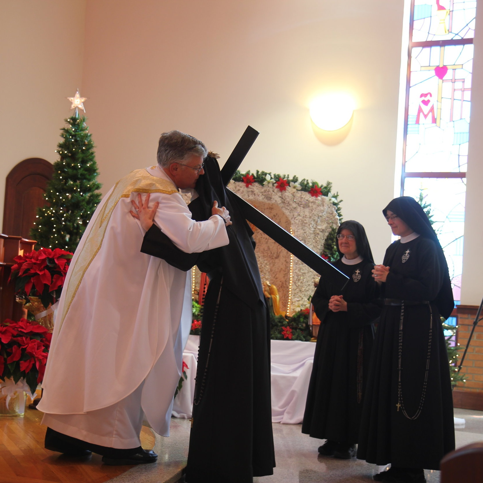 Sister exchanges the Sign of Peace with the Celebrants (con-celebrant Fr. John Shork, CP is pictured), her family, and her Passionist sisters