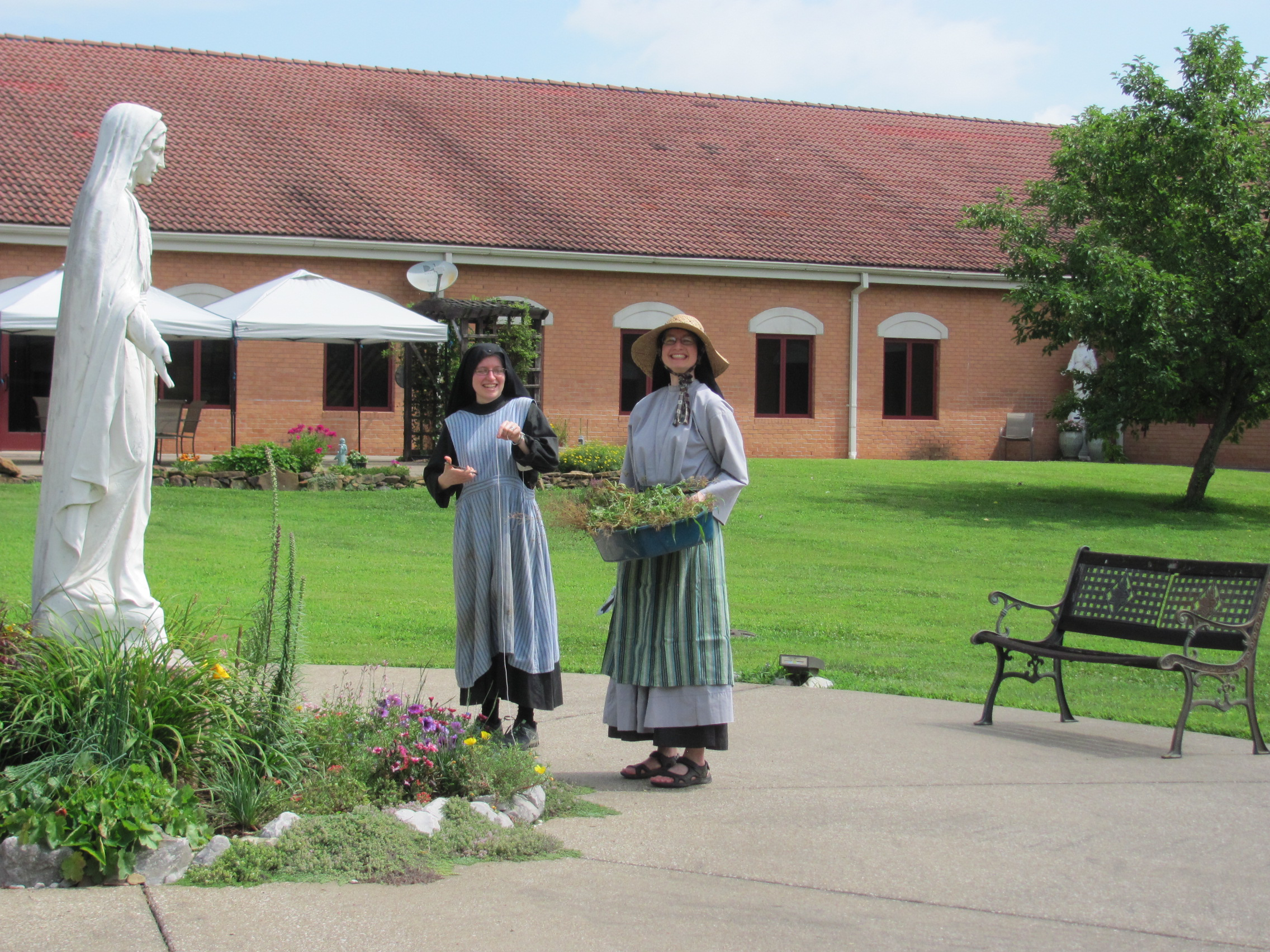 Sr. Frances Marie and Sr. Cecilia Maria gardening in the monastery courtyard.