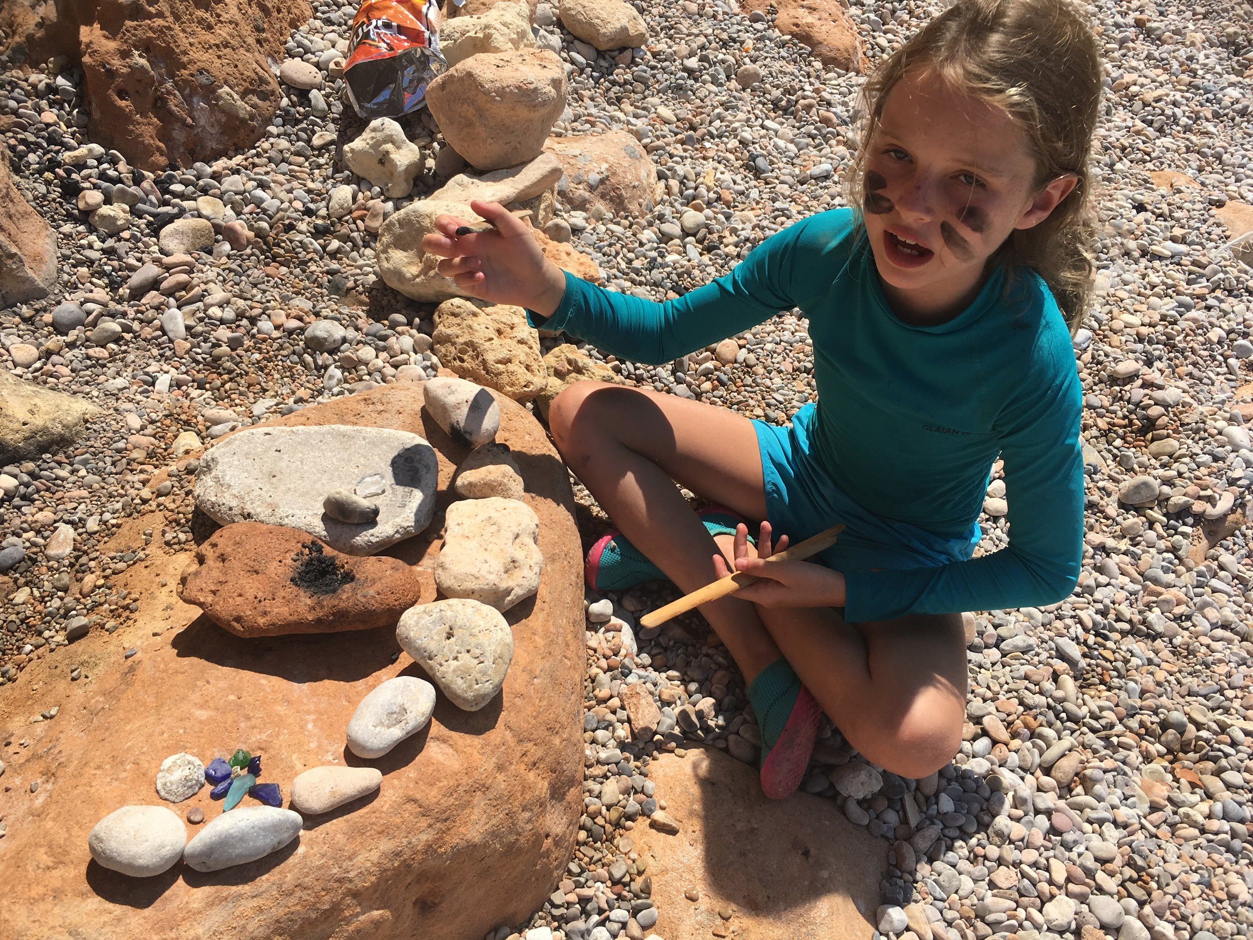 Here Izzy (and Victoria out of site of the photo) found a piece of burnt wood and made some type of potion along with finding colorful rocks. They found this spot on their own within view of our tiny camp on the beach. We encourage kids to explore and be creative with stuff they find on the beach. Still not sure what the story is with the charcoal face paint. It's a somewhat free range experience. (looks like they also manage to swipe a bag of Doritos!)