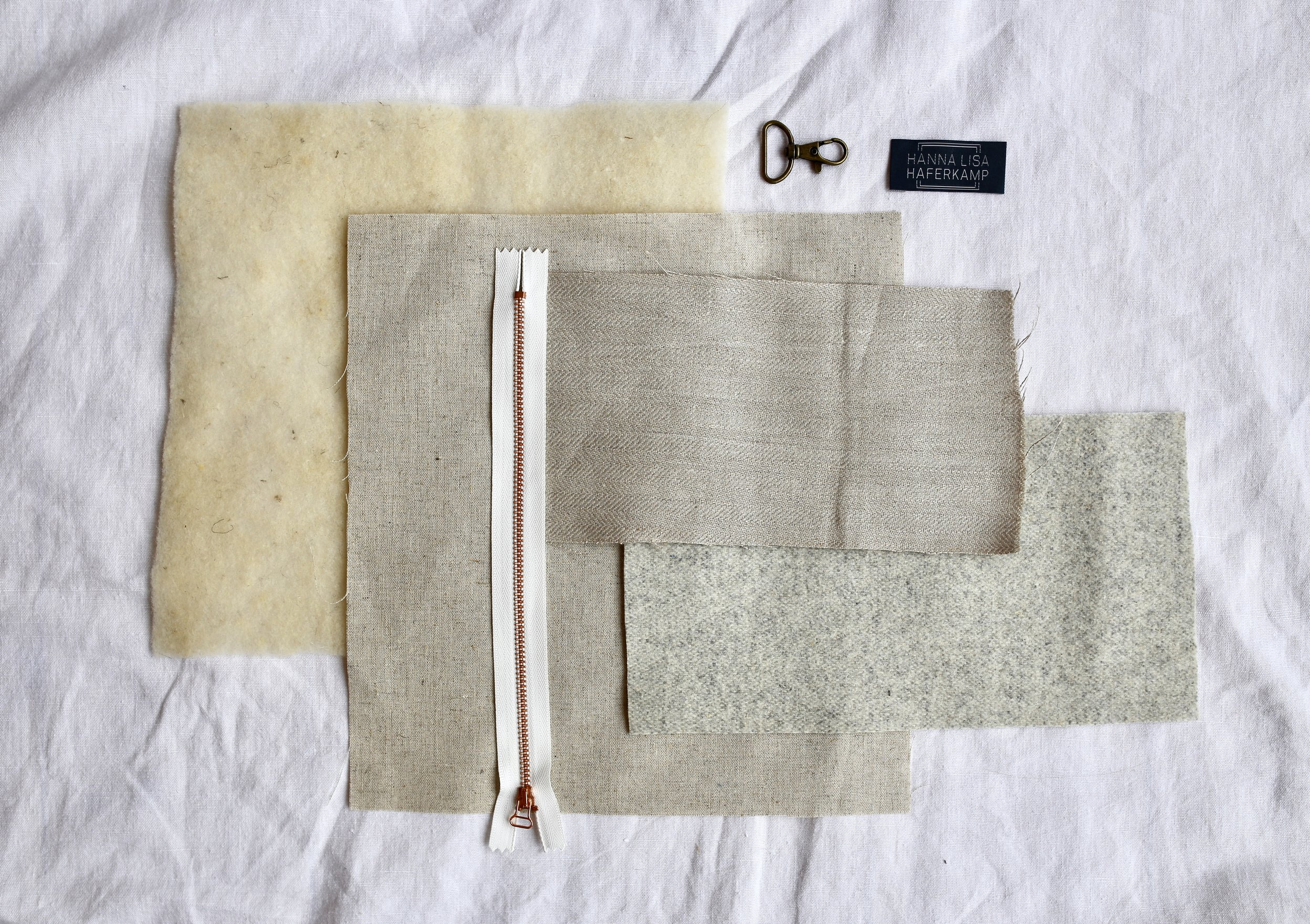 Loosely from left to right: Wool interfacing, linen & viscose lining, zipper, Austrian herringbone linen, wool contrast fabric, carabiner & label.
