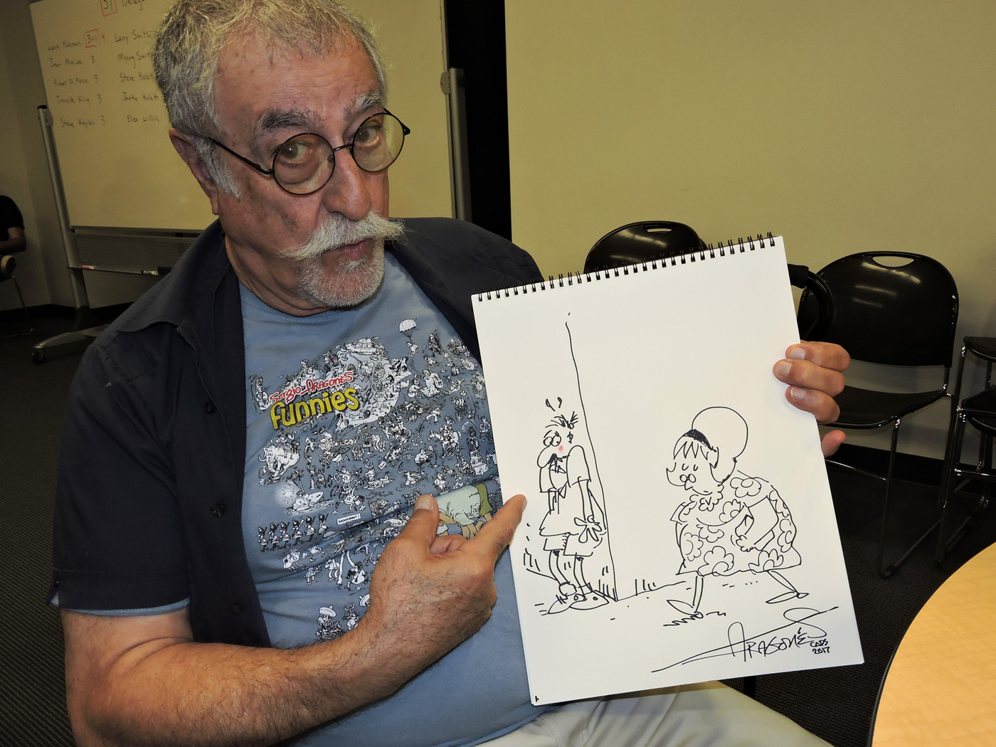 Sergio Aragonés with a 2018 drawing of Fanny Hillman done exclusively for  Hogan's Alley , the first time in years Aragonés had drawn the character. Photo by David Folkman