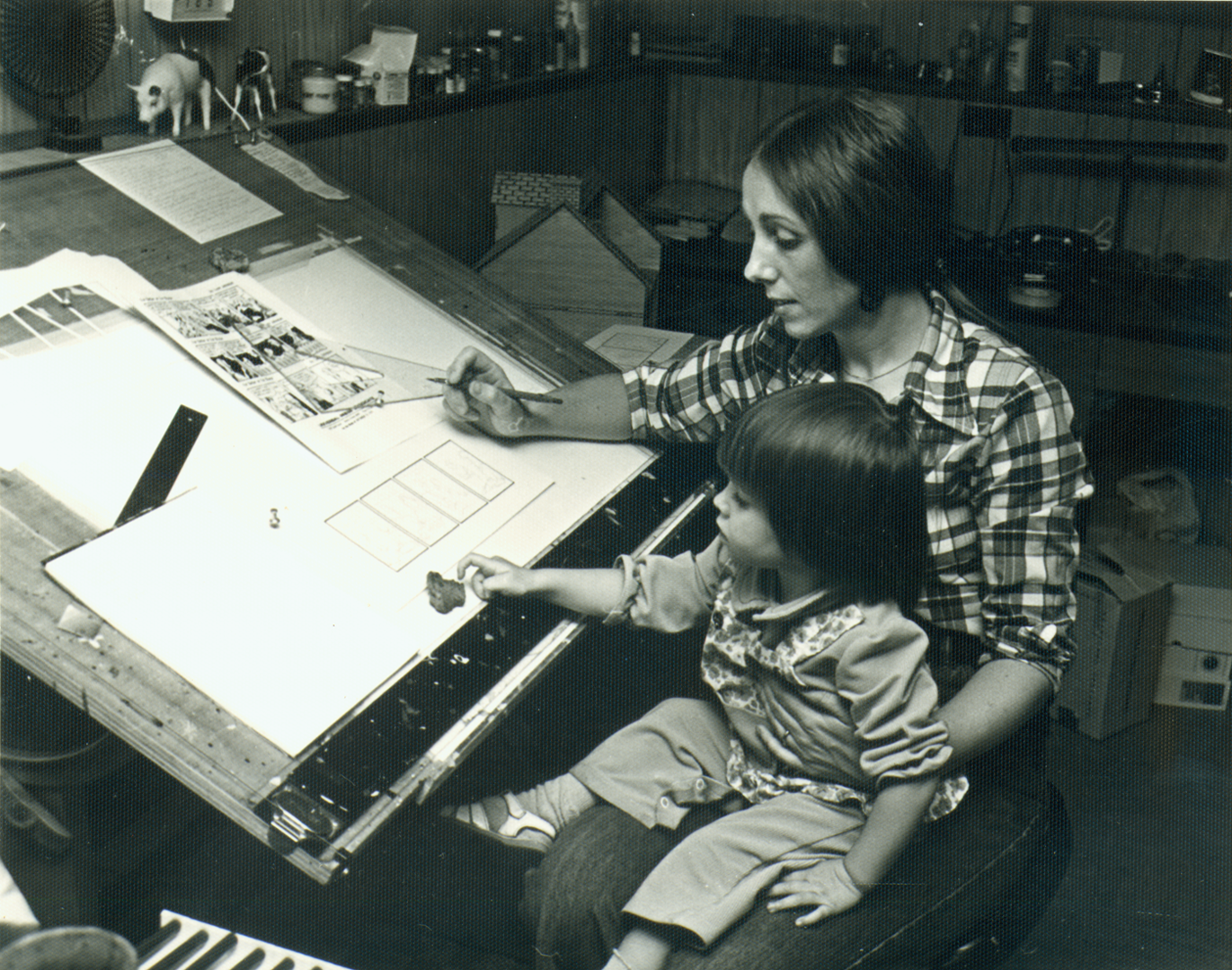 Lynn at the drawing board with daughter Kate in her lap.