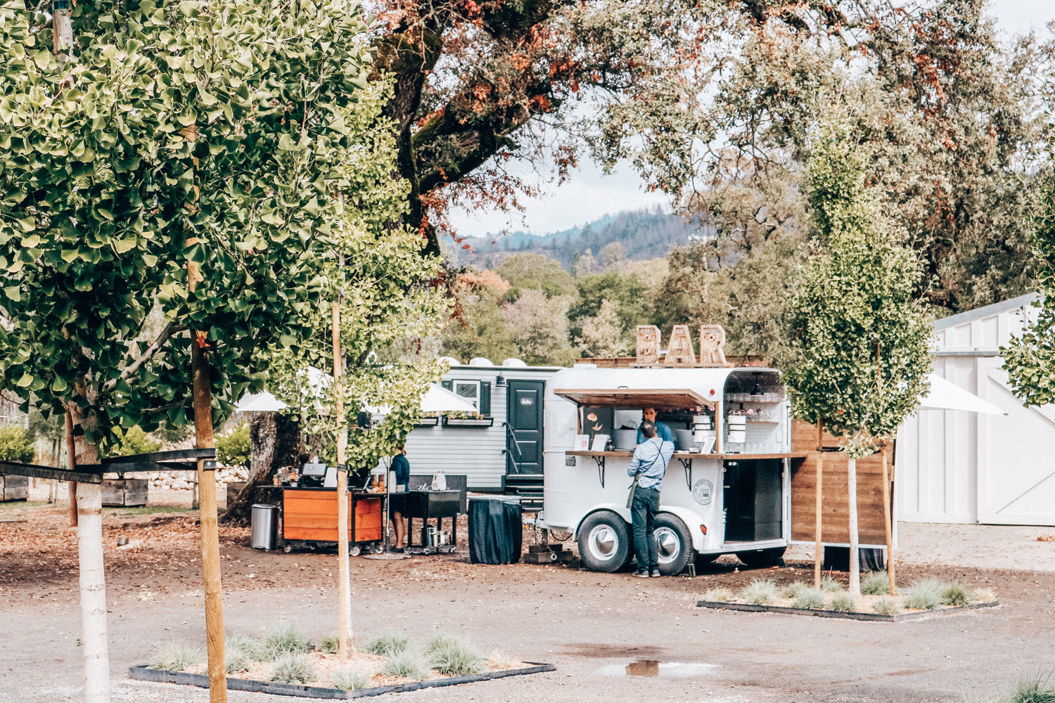 """Coffee & tea cart on the left, adorable portable restrooms in the middle/back, and """"bar"""" cart on the right with water and tea until happy hour. Photo via Kessler Ramirez"""