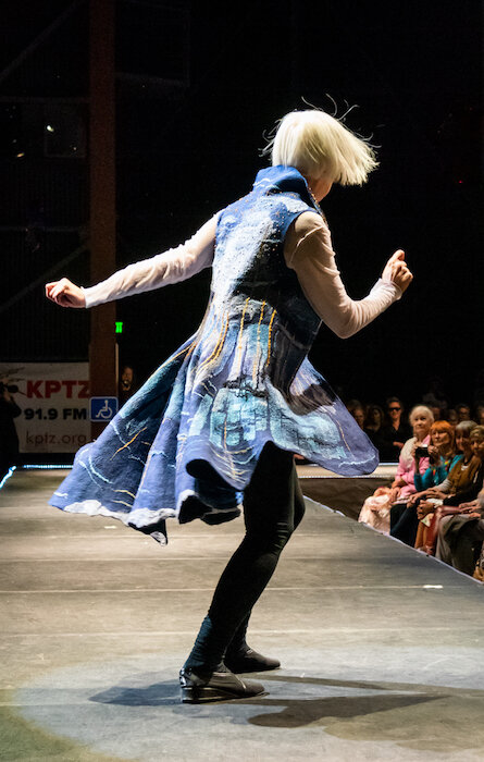 Starry Night Over The Rhône  2019 Donna Lark and Pat Herkal  Port Townsend doelark@gmail.com spherkal@gmail.com  A collaboration by two SDA-NP members, inspired by an 1888 Van Gogh painting of the same name, this elaborate, though wearable, vest was Nuno felted with merino wool roving on hand-dyed silk by Donna.  Inspired by the colors and movement of the felting, Pat added the sparkle of the night via a plethora of beads.  Model: Barbara Ramsey Photo: Kay Harper
