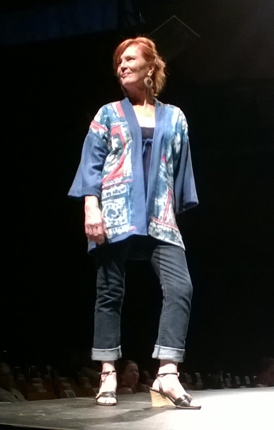 Shibori Jacket  2016 Diana Gipson  Port Townsend dianaoutdoors@att.net  Diana has transformed coffee bean bags, plastic construction fencing and silk into WAS runway-ready looks.  Traditional Japanese shibori designs were hand-stitched into silk, dyed by the artist and hand-appliqued onto a silk jacket to create this lively garment ideal for summer wear.  Model: Jan Burr