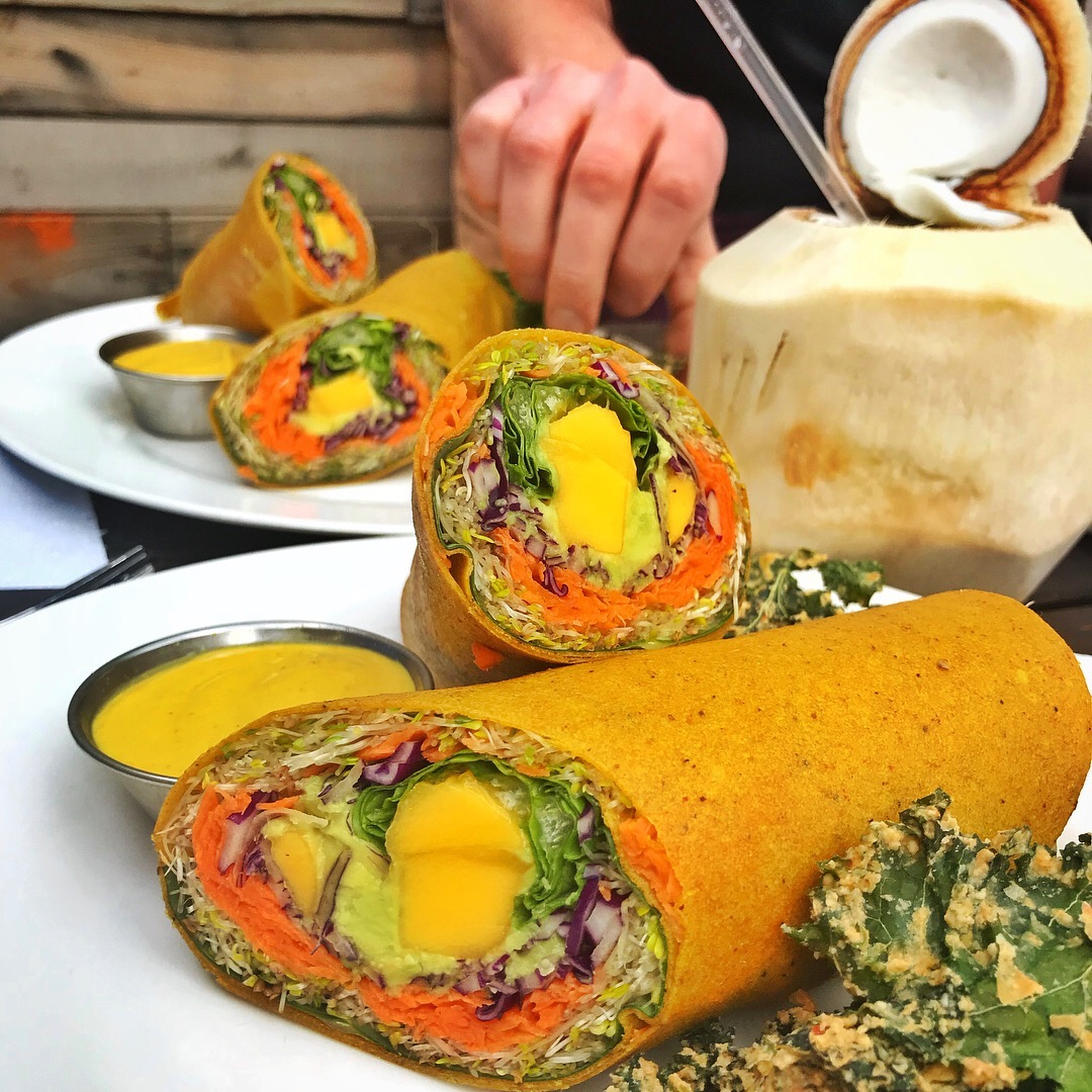 💚 Peace Pies - Come visit San Diego's only 100% raw vegan restaurant. They have two locations in Ocean Beach and in Encinitas. They offer a full menu consisting of salads, pizzas, wraps, entrees, dried goods, desserts, chocolates and accessories to aid in the live food lifestyle. Pictured to the left is the mango curry wrap with cheezy kale chips.