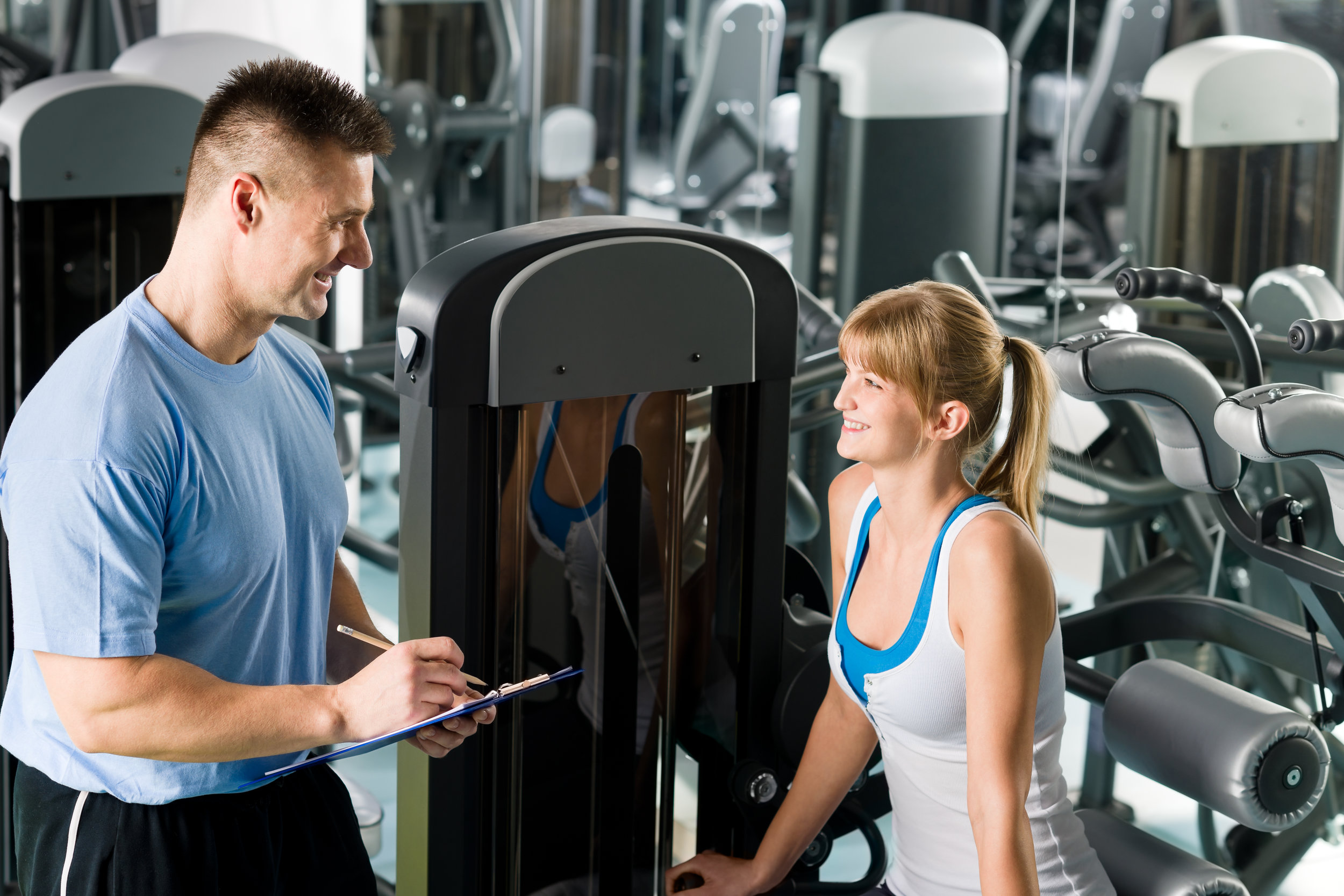 young-woman-with-personal-trainer-look-at-exercise-chart-at-gym_Htxg8mETVs.jpg