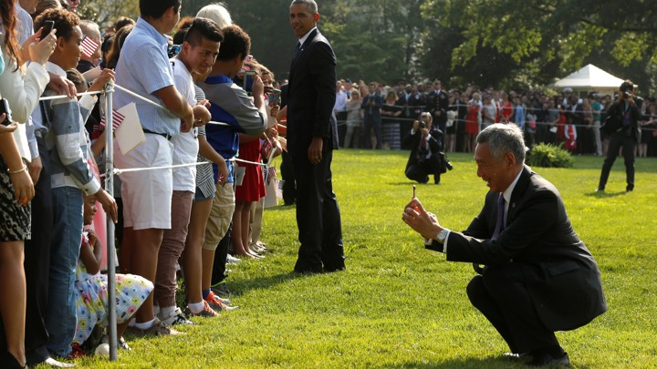 Singapore's prime minister Lee Hsien Loong squats to take a photo on the White House lawn REUTERS / JONATHAN ERNST