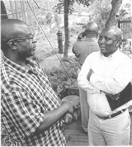 John Muhanji, left, Director of African Ministries for Friends United Meeting, talks to Ndanga Ramazani during a recent dinner gathering at Sue Tannehill's home.
