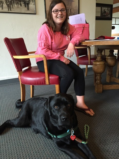 Sarah Brinson and Oscar who is a one year old English black Lab.
