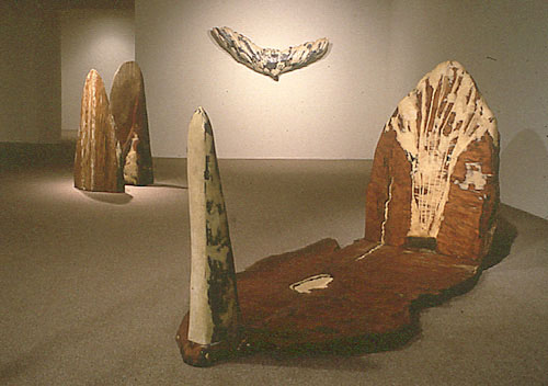 """Installation at Mincher-Wilcox Gallery, San Francisco, 1990 """"Hand / Wing"""" (left), """"John Crow"""" (on wall), mixed media, 33 x 78 x 8 inches """"Sun Dial"""" (right), redwood, 58 x 98 x 48 inches"""