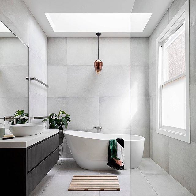 A few things we admire about this bathroom: 1. Large grey square tiles, resembling a nice natural stone texture. 2. Minimalist mirror, complemented by an elegant polished copper light fixture above the contemporary tub. 3. Skylight above the tub and large adjacent window to provide daylight to this beautiful bathroom. We never underestimate the utilization of daylight. This is our inspiration. . . . . #tribecakb #elegant #luxury #interiordesign #newyork #marble #tile #bathroom #kitchen #kitchen&bath #sophisticated #modern #contemporary #rich #remodeling #tribeca #designer #archidigest #architecture  #building #black #nyc #brookyln #lifestyle