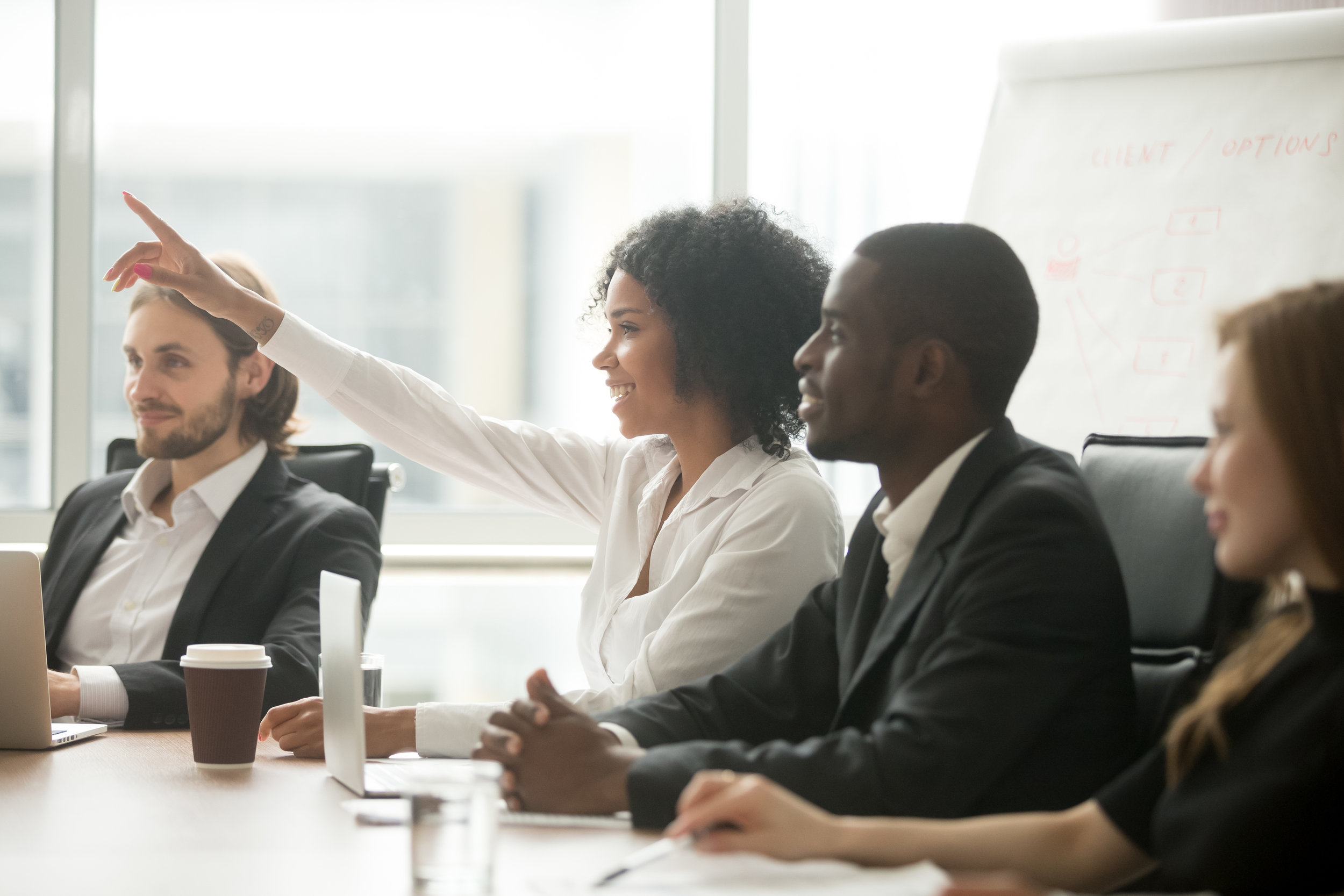 Copy of Copy of African woman raising hand to ask question at team training, curious black employee or conference seminar participant vote as volunteer at group office meeting with multiracial diverse businesspeople