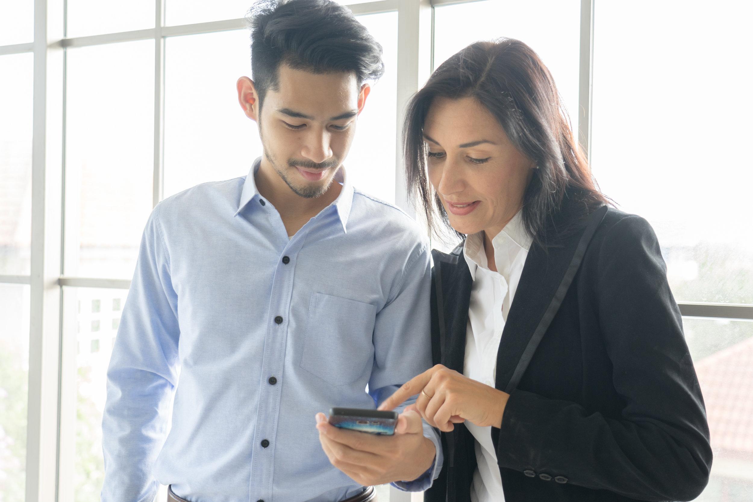 Business man and woman wearing suit, looking smartphone. Open space loft office. Panoramic windows background.