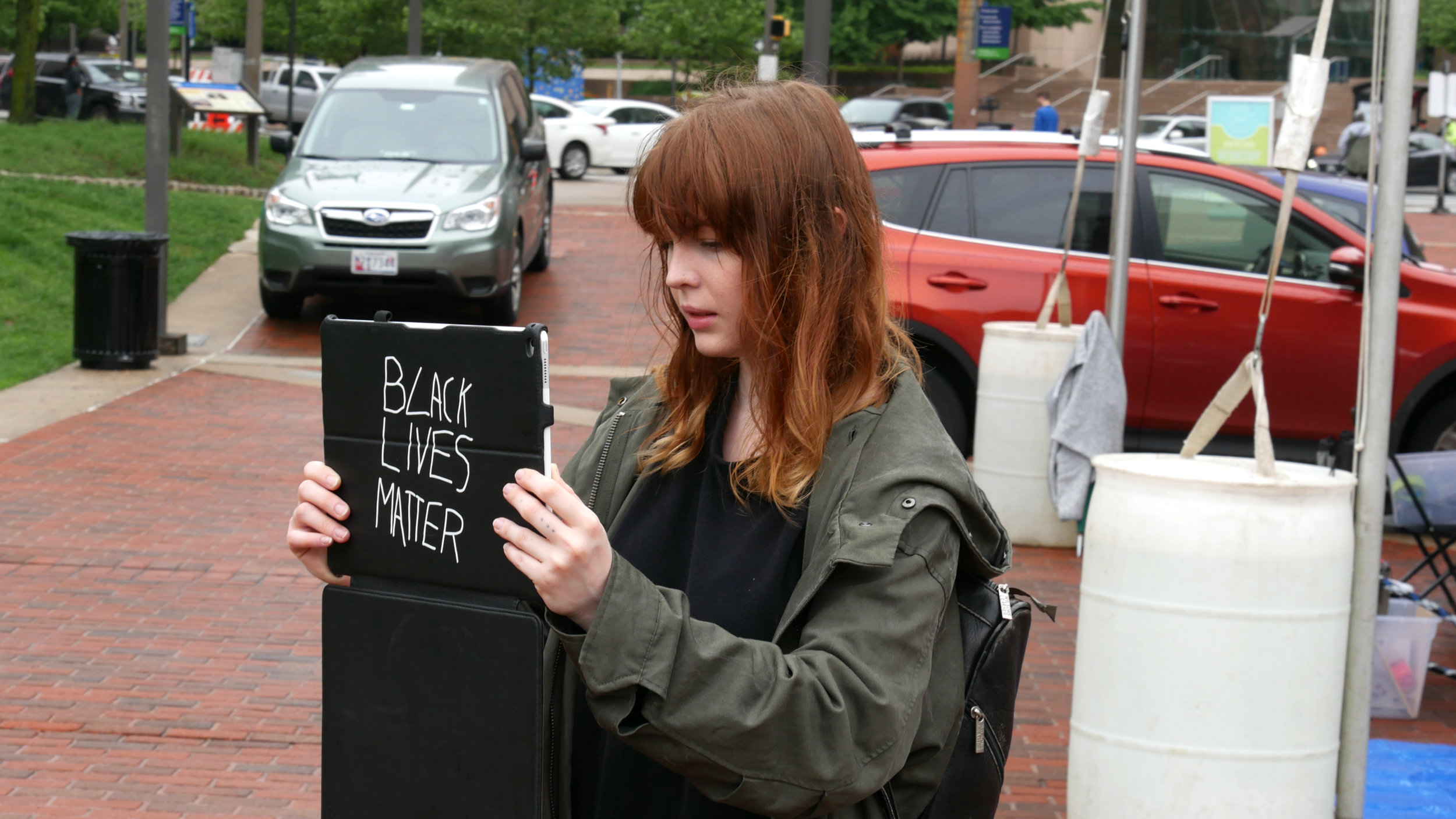 Maura Callahan holding an iPad like a protest sign and bringing back McKeldin Fountain. McKeldin Square, May 19 2018. Photograph by Timothy Nohe. © nonument01.org 2018