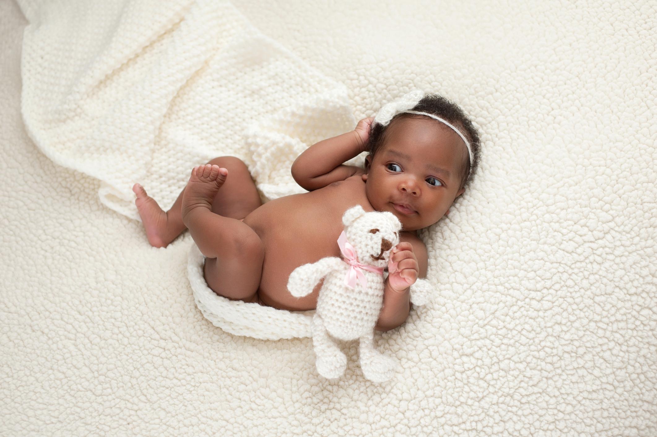 black baby with a teddy bear on a cream background