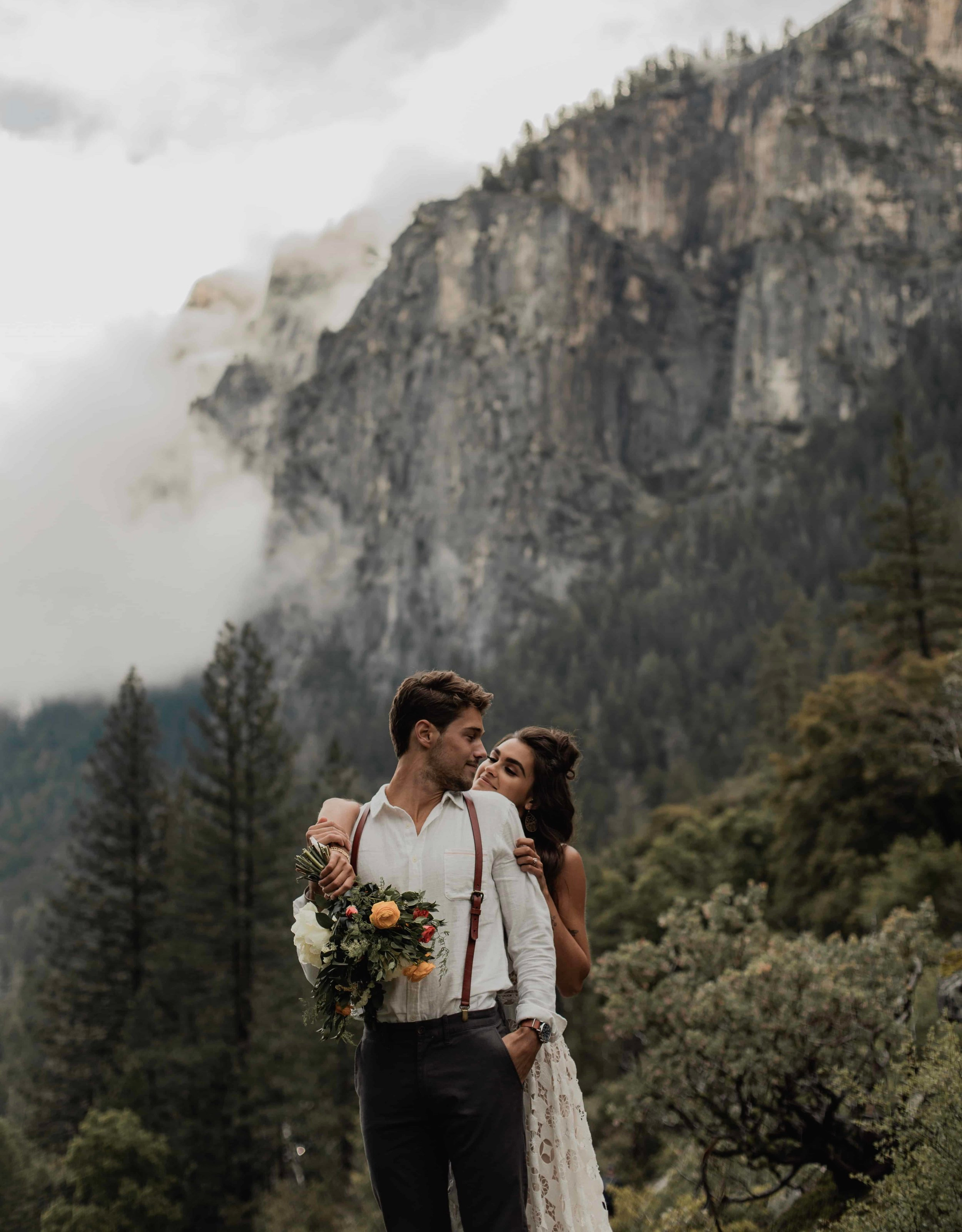 couple eloping in europe in the mountains looking at each other