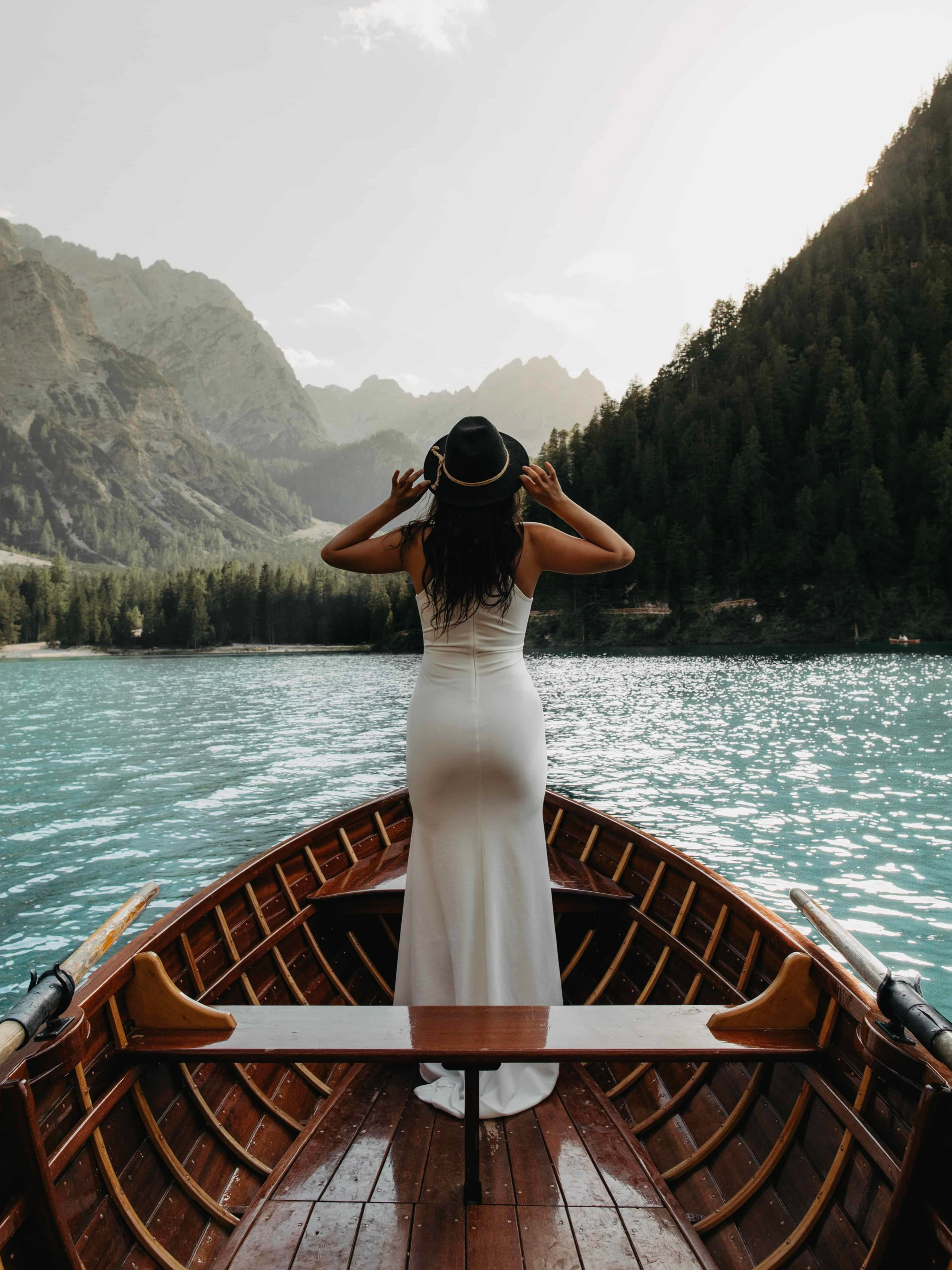 europe elopement bride in wedding dress turned away looking at mountains in a row boat