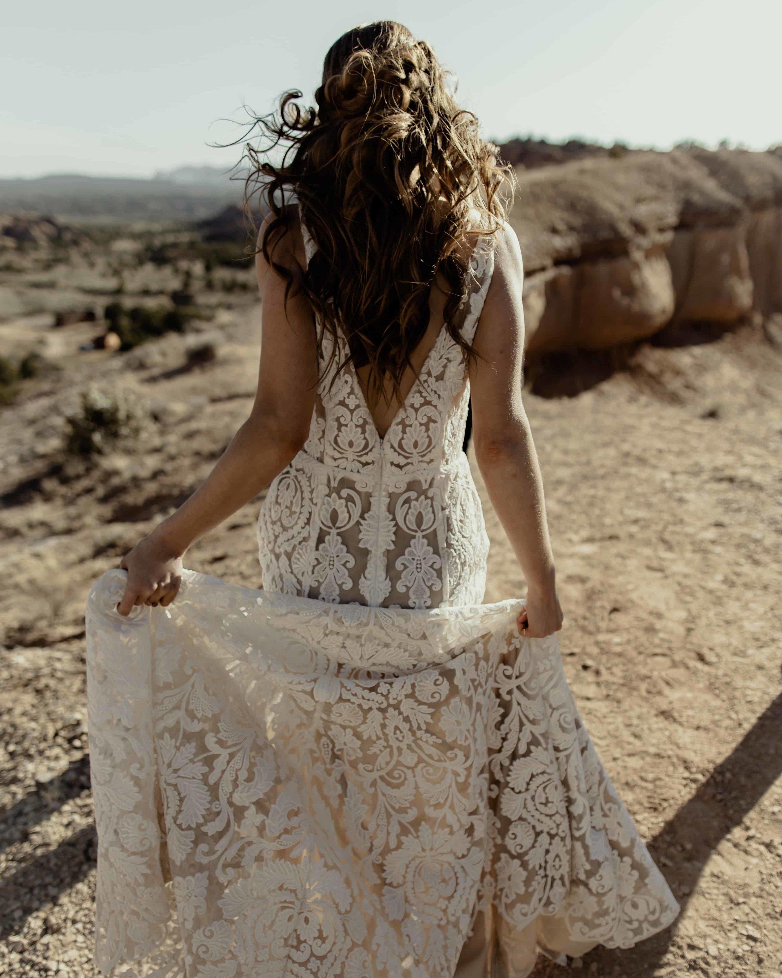 bride walks away holding her dress as she walks through the dirt in the desert