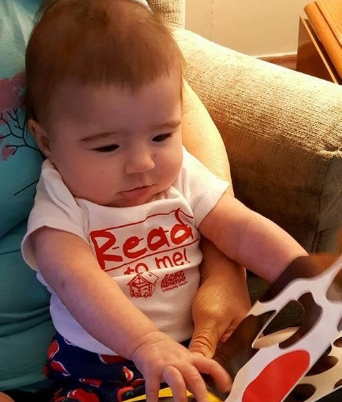 "Baby wearing a ""Read to me"" shirt while being read a book aloud."