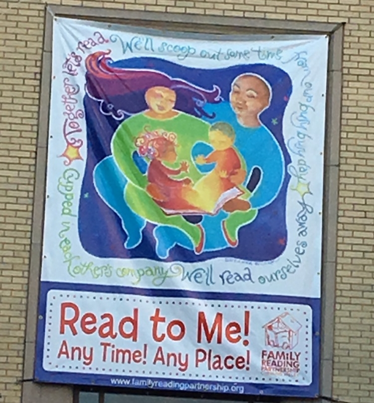 Read to Me Any Time Any Place banner posted on side of building.