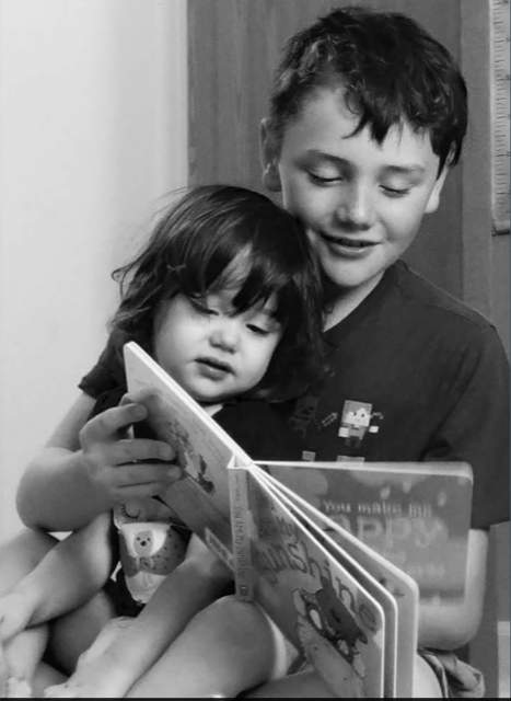 Black and white photo. Boy reading book to girl toddler
