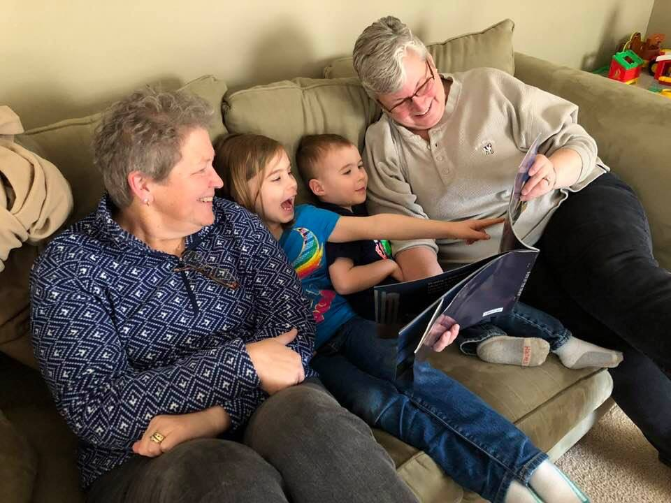 Family reading a book to two young children. It's a joyful experience!