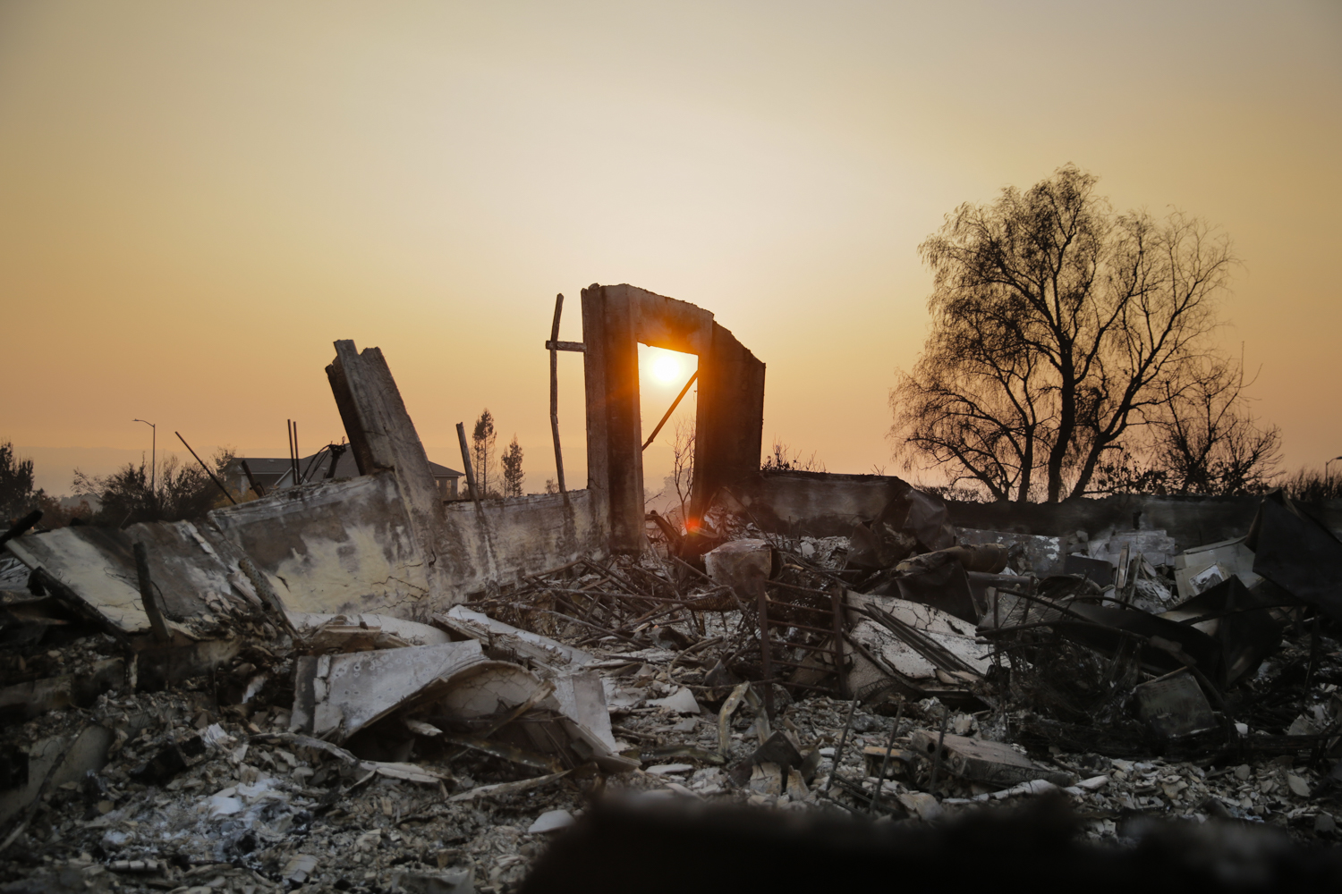 The sun is seen through an arch in the remains of a home in the Fountaingrove neighborhood in Santa Rosa, California
