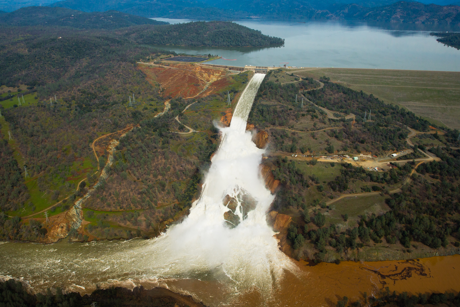 Oroville lake, the emergency spillway, and the damaged main spillway are seen from the air in Oroville, California