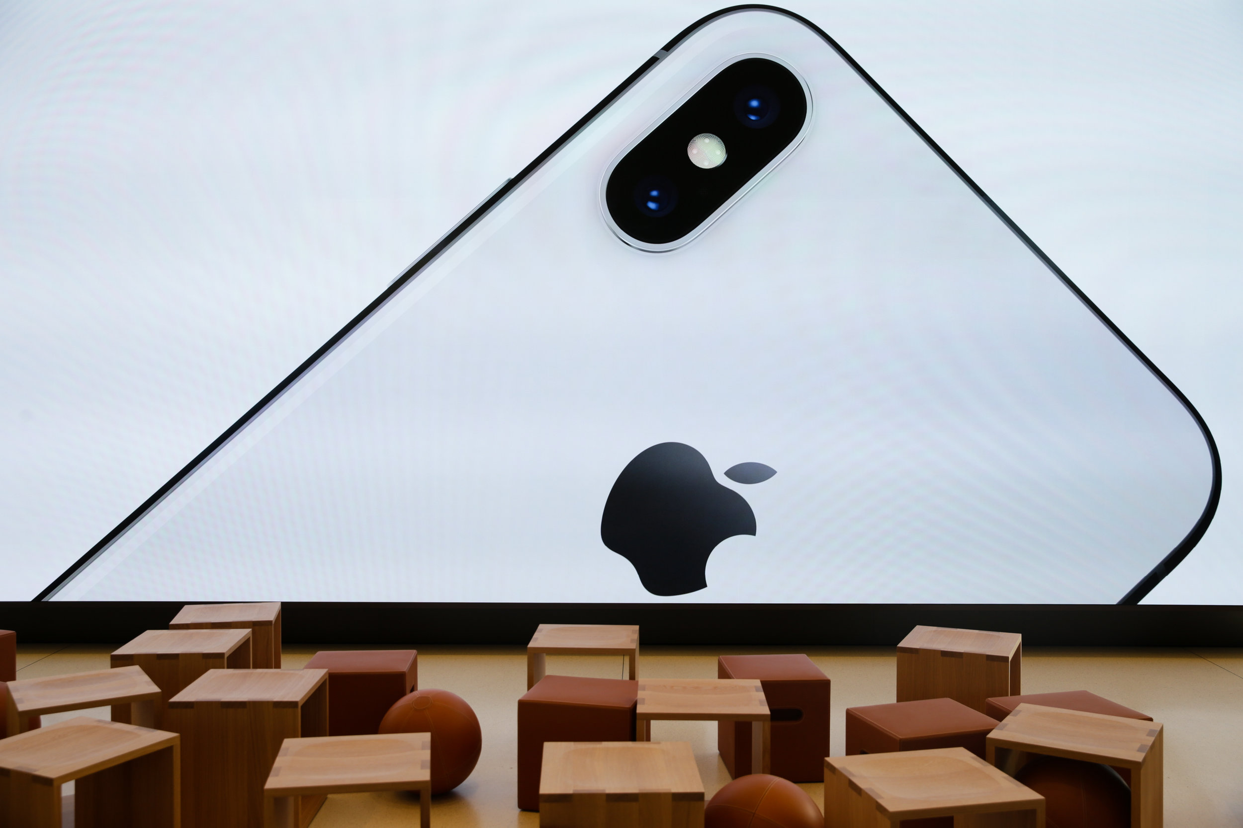 A large screen displays an image of the iPhone X at the Apple Park Visitor Center in Cupertino, California