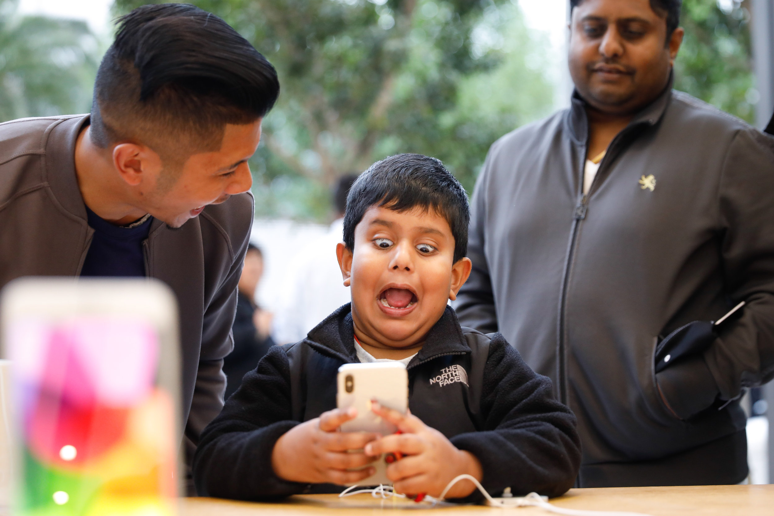 A boy uses the Animoji feature of the iPhone X on the first day of sales at the Apple Store Union Square in San Francisco, California