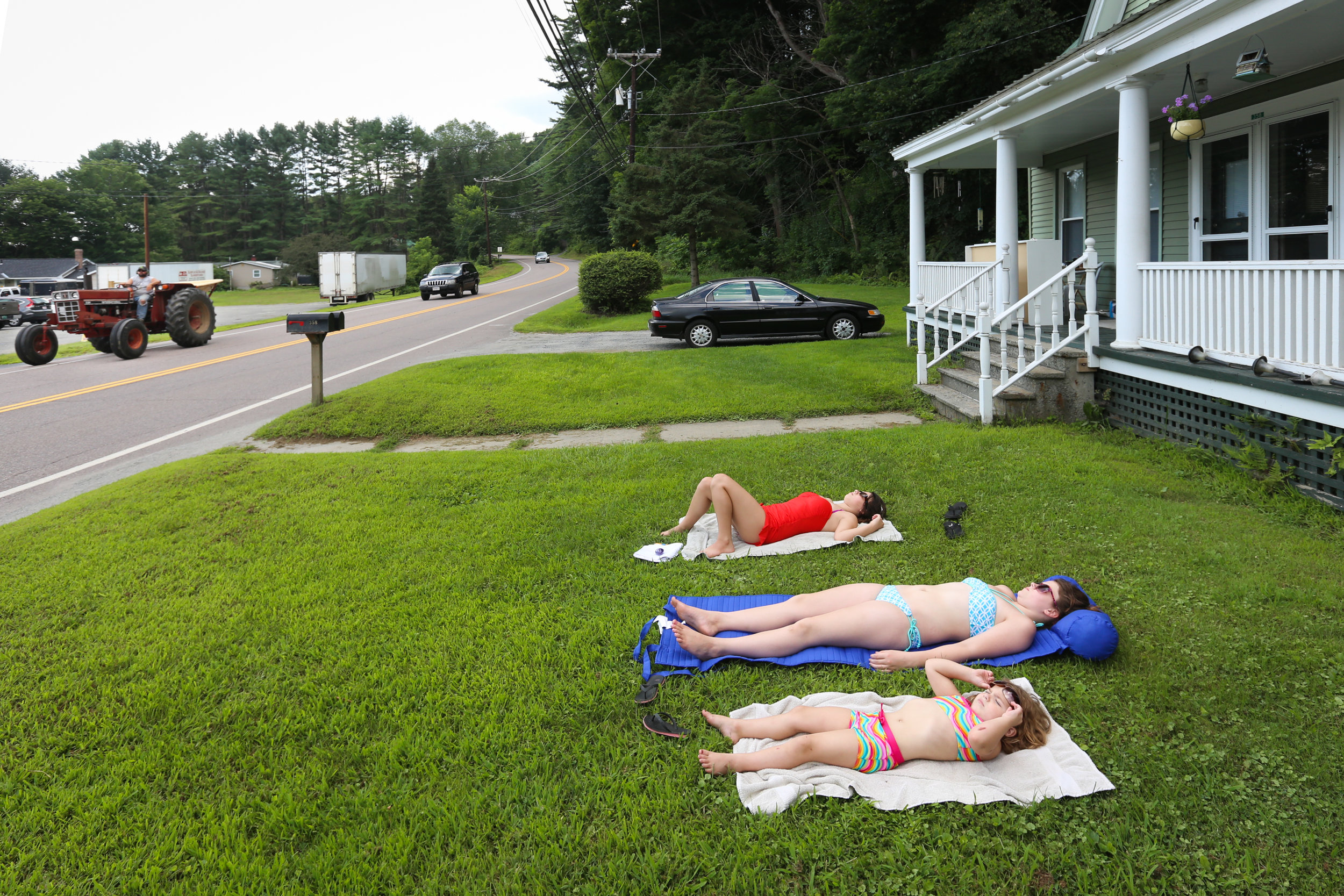 Madison Garrow, Lylah Reynolds, and Sadie Garrow, sunbathe on the front lawn of Reynolds' home in Windsor, Vermont