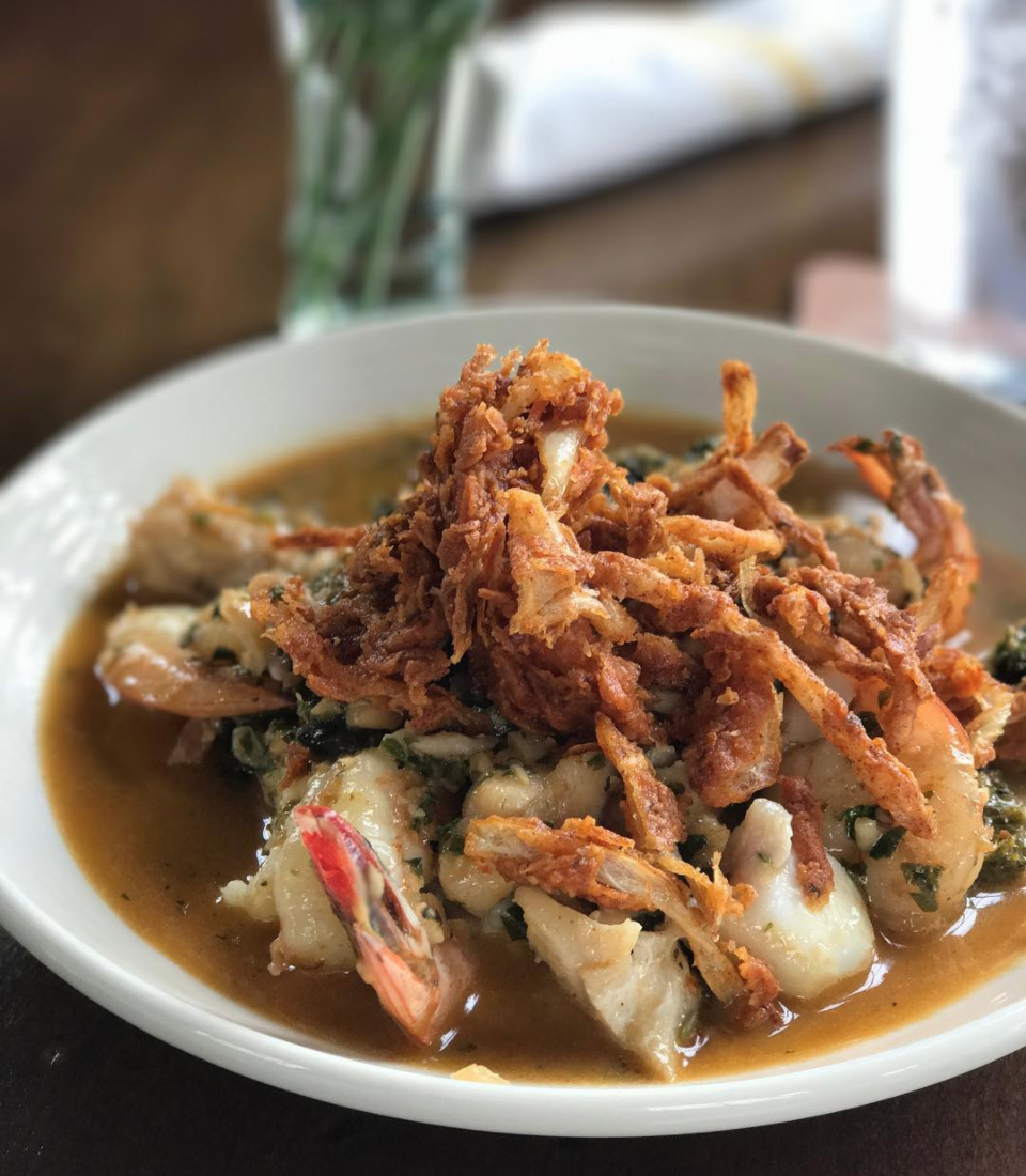 Fish and shrimp on a bed of grits and collard greens)