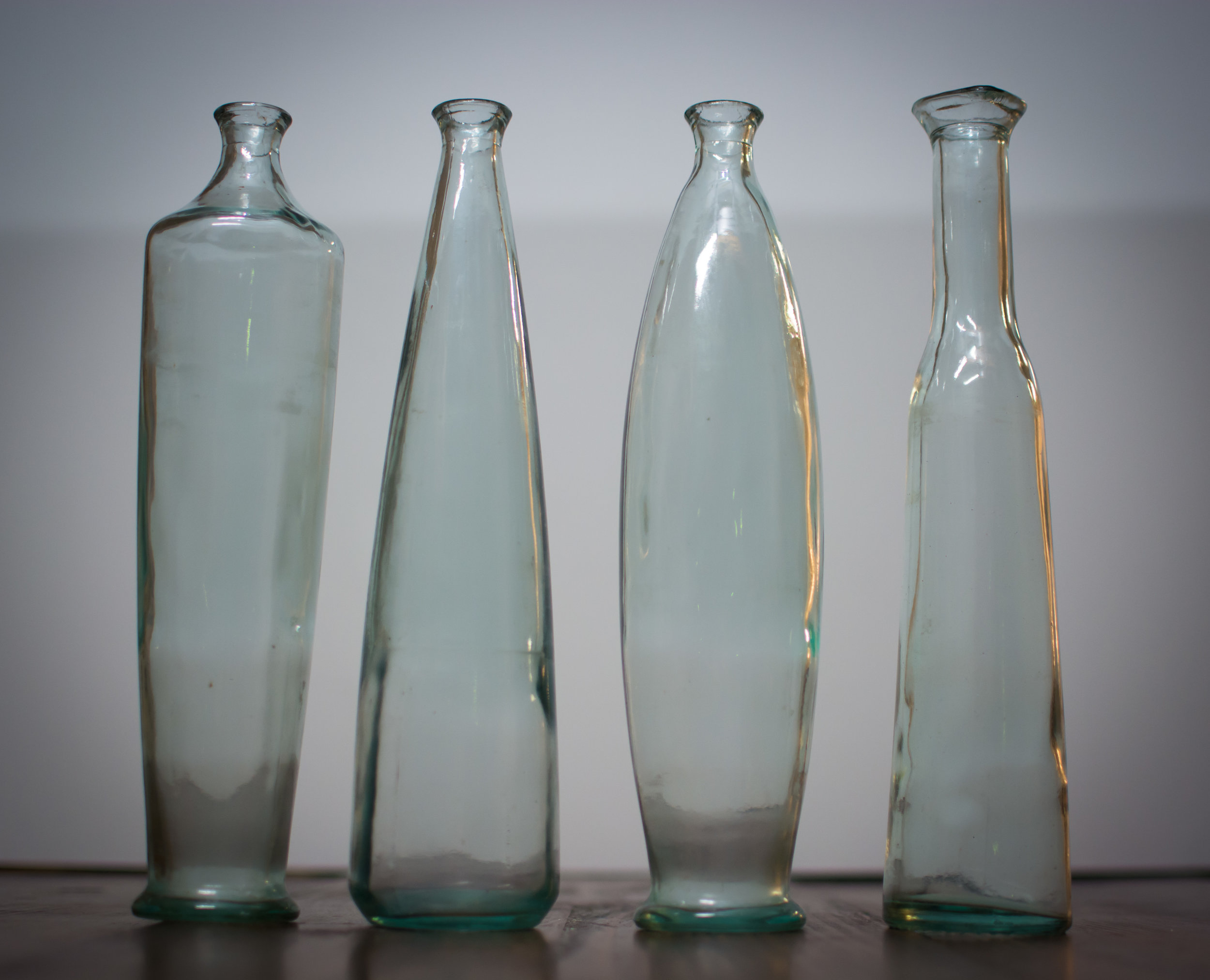 Set of 4 Mismatched blue tint vases   height-  Price: $12 set/ $3.00 each  Inquire about quantity and availability.