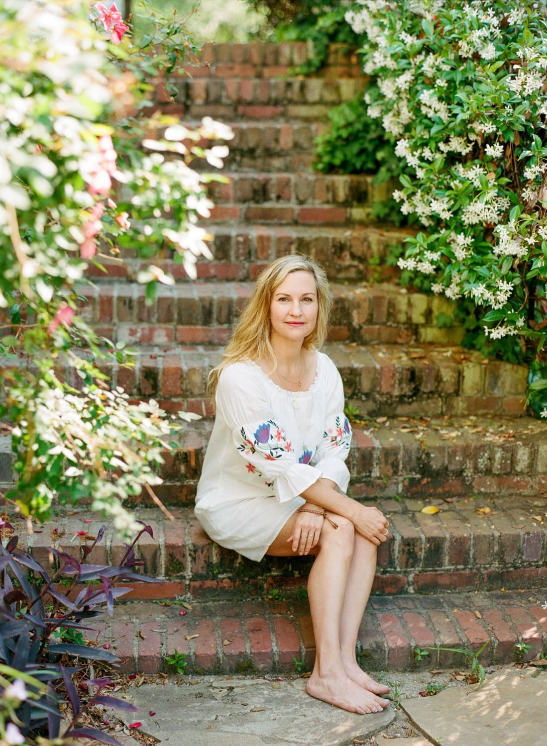 photo of honor hawkins holictic wellbeing coach sitting in stair and surrounded by flowers