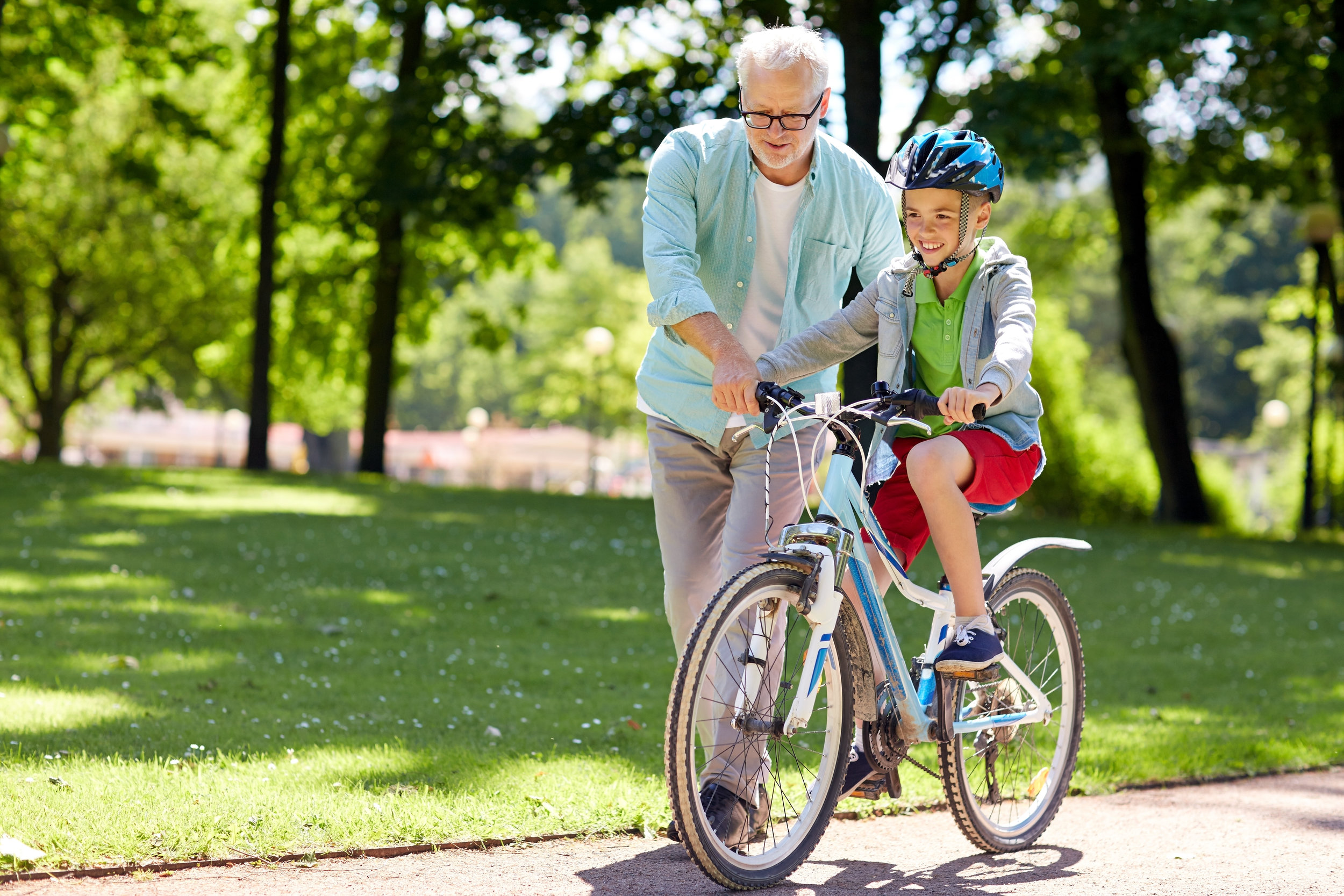 Adult teaching boy how to ride a bike